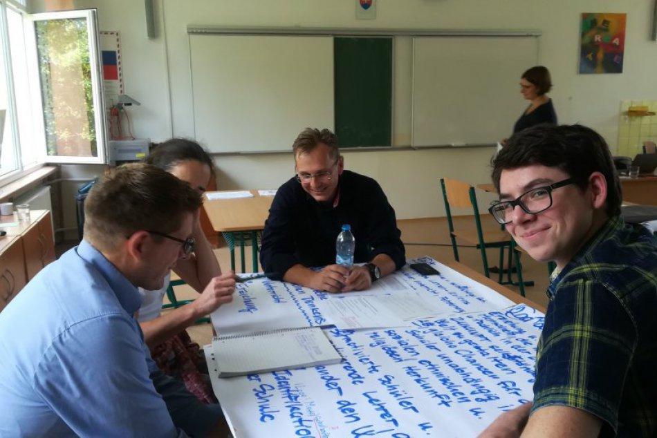"""Ilustračný obrázok k článku Workshop na popradských """"bilinkách"""". Za jedným stolom učitelia, rodičia i žiaci"""